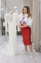 مارسيلا لاتي ، صاحبة صالون جيرالدينا سبوسا، تعرض أحد فساتين الزفاف التي وصلتها حديثا في صالونها في تيرانا. (ا ف ب)