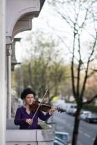 عازفة الكمان بالأوركسترا في مولهاوس جيسي كوخ تقدم عزفا موسيقيا من شرفتها كل يوم لدعم العاملين الصحيين في تولوز بشرق فرنسا.    (أ ف ب)