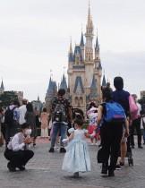 زوار يلتقطون صورًا عند وصولهم إلى طوكيو ديزني لاند في أوراياسو بعد إعادة فتحها رسميًا بعد أربعة أشهر من الإغلاق بسبب تفشي فيروس كورونا.ا ف ب