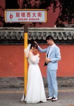 زوجان يقفان خلال جلسة تصوير قبل الزفاف في بكين.   ا ف ب