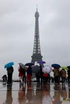 سياح يقفون حاملين المظلات تحت المطر بالقرب من برج إيفل في ساحة تروكاديرو في باريس. (أ ف ب)