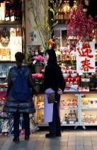بائعة تتحدث إلى عميلة في متجر لبيع الزهور والزخارف الخاصة بالعام الجديد بأحد مراكز التسوق في طوكيو. (رويترز)