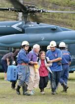 أفراد من قوات الدفاع عن النفس اليابانية يساعدون زوجين مسنين بعد أن تم إجلاؤهم بطائرة هليكوبتر عسكرية من منطقة كارثة بعد هطول أمطار غزيرة في محافظة كوماموتو.   (ا ف ب)