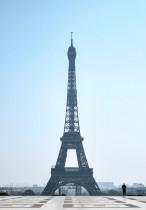 شرطي يسير بالقرب من برج إيفل التاريخي في باريس والمهجور حاليا بفعل المخاوف من انتشار فيروس كورونا.(أ ف ب)