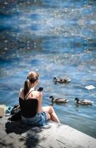 امرأة تستمتع بالشمس في باريس على ضفاف نهر السين بينما يسبح البط أمامها، حيث تخفف فرنسا من إجراءات الإغلاق. ا ف ب