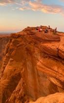 سائحون يسيرون إلى حافة الجرف للاستمتاع بمنظر رائع لجبل متعرج محفور الشكل لنهر كولورادو ، في بلدة بيج - أريزونا. ا ف ب