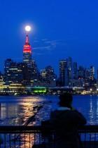القمر يضيء خلف مبنى إمباير ستيت بينما يضيء المبنى باللون الأحمر للتضامن مع المصابين بفيروس كورونا في حي مانهاتن بمدينة نيويورك. رويترز