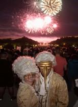 المشاركون يرتدون أزياء مثل تلك التي يرتدونها في فرساي خلال فترة الملك لويس الرابع عشر أثناء حضورهم الألعاب النارية  جراند بال ماسك  أمام قلعة فرساي ، فرنسا. (رويترز)