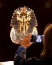 امرأة تلتقط صورة لقناع متماثل بالحجم الطبيعي لملك مصر الفرعوني توت عنخ آمون خلال عرض إعلامي لمعرض توت عنخ آمون: قبره وكنوزه، في زيوريخ ، سويسرا.   (رويترز)